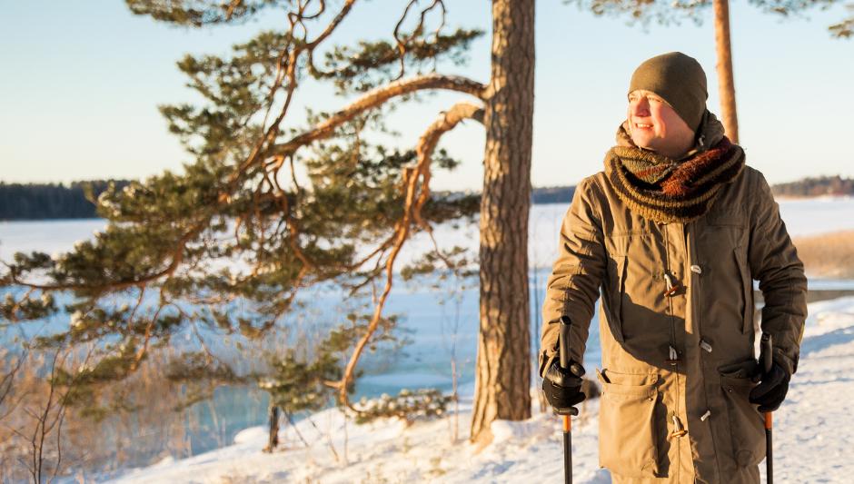 Mies sauvakävelee talvisessa maisemassa
