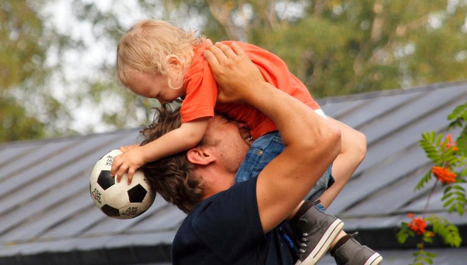Isä nostaa poikaa ilmaan